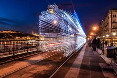 A long exposure photo of a moving trolley in Budapest lit up with over LED lights. It looks like it's moving through space and time!