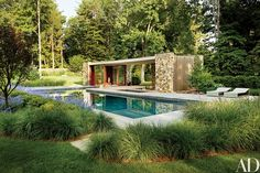 A poolhouse in Westport, Connecticut, designed by the New York City architectural firm SPaN, is distinguished by fieldstone walls and a slatted cedar pergola | archdigest.com
