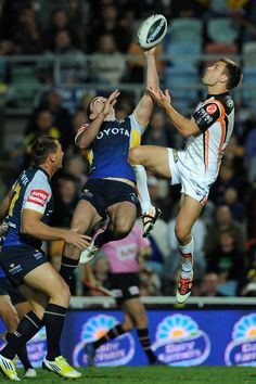 Kane Linnett of the Cowboys competes for the ball with Beau Ryan of the Tigers during the round 20 NRL match between the North Queensland Cowboys and the Wests Tigers at Dairy Farmers Stadium on July 2012 in Townsville, Australia. Rugby League, Rugby Players, Cowboys Men, Dallas Cowboys, Wests Tigers, Australian Football, Beefy Men, Athletic Men, My Boys