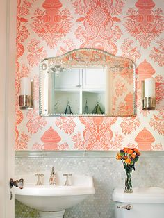The inspiration was daring wallpaper, City Park from Flavor Paper, that features fire hydrants, parking meters, rats and pigeons and is printed in custom white and tangerine. Alan added mother-of-pearl coin tile as a tall wainscoting and a vintage mirror she found in a flea market.