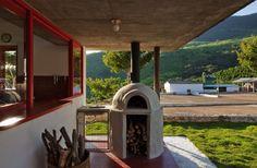 Casa em meio às serras é refúgio tranquilo com jeito mineiro. Uma das atrações da casa Dom Viçoso, projetada pelo arquiteto Marcelo Ferraz, é o forno a lenha instalado em uma das varandas.  Fotografia: Nelson Kon/ UOL.