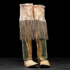 thread and sinew-sewn hide with coatings of red, yellow, and green pigments; beaded detailing executed in colors of pony trader blue, rose, and white; 59 and 63