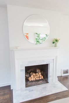 Modern white marble fireplace and circular mirror with no frame: http://www.stylemepretty.com/living/2016/08/31/the-perfect-color-combo-for-an-eternally-bright-and-happy-home/ Photography; Emma Rose - http://emmaroseco.com/
