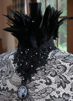 A gorgeous couture statement piece with black beaded lace, satin rosettes, rhinestones and uber chic feathered collar. Complete with cameo for added Victorian charm.