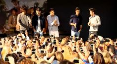 """Watch Directioners go wild in Cologne Germany as Harry, Liam, Zayne, Louis, and Niall visit for a signing and promote their newly release single """"Live While We're Young""""."""