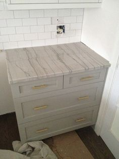Pulls: 306 pulls from Colonial Bronze; counter: Luna de Luce/ Bianco Macaubas quartzite; cabinets: Benjamin Moore's Cape May Cobblestone
