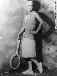 Tennis champion, Suzanne Lenglen, who won Wimbledon from 1919-1926, had a close association with couturier Jean Patou, who dressed her both on and off court. Here she is modelling a tennis outfit by Patou. Over her pleated dress she wears a sleeveless sweater, derived from a man's waistcoat, and around her head a bandeau, a style that was much copied.