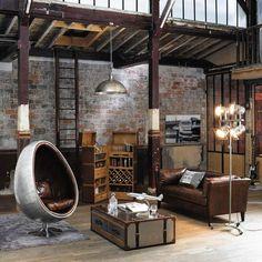 déco industrielle dans le salon aménagé avec une table basse style industriel en malle métallique, fauteuil egg en métal et cuir et mur de brique