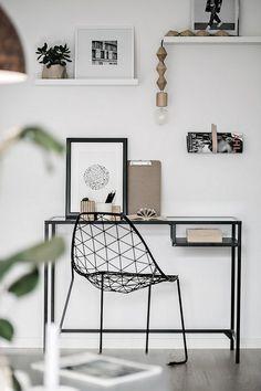 Un coin bureau dans un salon déco minimaliste et scandinave en noir avec des détails en bois pour bien se travailler