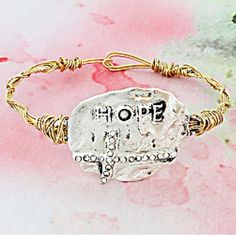"""#299 Hammered Silver Cross Hope Goldtone Bangle This bracelet will add character to any outfit! Hammered Silvertone Plate with Cross * Faux Crystal Accents on Cross * Goldtone Twisted Wire Band * Raised """"Hope"""" * Hook Closure * 2.75"""" Diameter Jewelry"""
