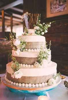 three-tiered wedding cake with burlap wrapped tiers, fresh white ranunculus, and greenery accents