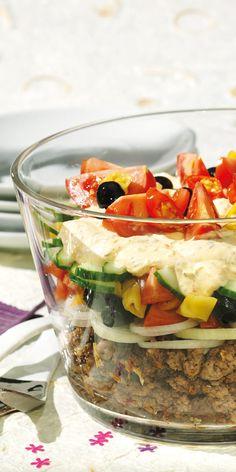 Dieser sommerliche Schichtsalat holt ein Stück Griechenland an den Tisch. Köstlich angerichtet mit Oliven, Hackfleisch und Tomaten.