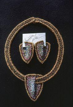 Elizabeth Tuttle, Shield Collar and Earrings; Crocheted cotton sewing thread Glass beads. 1982 to 1990 #crochet #art #fineart #fiberart #fibreart #textile #textileart #domesticlife #domesticart #conceptualart #design #beadwork #beading #jewelery #wearableart Conceptual Art, Textile Art, Wearable Art, Fiber Art, Pattern Design, Jewelery, Glass Beads, Arrow Necklace, Sewing