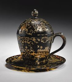 A RARE ITALIAN GOLD-INLAID TORTOISESHELL COVERED CUP AND SAUCER, MADE FOR THE OTTOMAN MARKET, PROBABLY NAPLES, SECOND HALF 18TH CENTURY of typical form, wholly composed of tortoiseshell, the handle ridged and studded with gold- inlay, the cover with a bud finial, decorated throughout with gold-inlaid baroque foliate motifs and architectural vignettes 14.5cm. max. height.