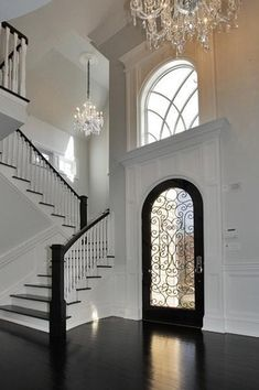 Traditional Entryway with Crown molding, High ceiling, Wainscotting, Monochromatic, Chandelier, French doors, Metal staircase