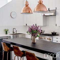 O uso de peças em metal, como as banquetas e os pendentes, garantem um toque industrial à cozinha