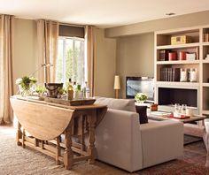 Una mesa plegable  Si tu salón comparte espacio con el comedor, pero coméis en el office, una buena idea es liberar el espacio con una mesa plegable que puede tener un doble uso: en este caso, de trasera del sofá, donde apoyar una lámpara para leer cómodamente.