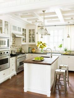 white cabinets, warm wood countertop and floors, stainless appliances + chrome pendants = timeless design
