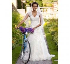 I know vintage bikes are becoming a new wedding thing, but how on earth is she going to get her dress over the top tube?