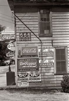 April 1938. Store in Halifax, North Carolina, with signs advertising carbonated beverages and patent medicines. -- Does the Anti-Christ shop here?
