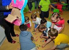 Дети разбили пиньяту и собирают конфеты