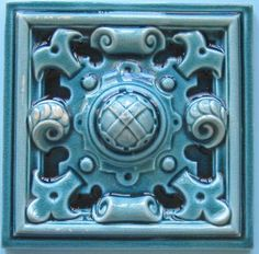 """A very deep relief carved gothic style tile in a deep turquoise majolica glaze. The tile is imprinted """"Wedgwood"""" on reverse and was slip cast rather than dust-pressed as most other tiles of the time were."""