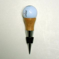 "Official Championship Golf ball mounted atop a Maple wood ""tee and a bottle stopper. Other stoppers from Walnut, Apple, and Red Oak woods at the same Etsy website."