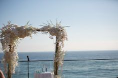 Beautiful wedding arch made of orchids, white roses, gardenia and white hydrangea //  Nicole Caldwell Photography