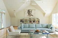 Living room with long light blue sofa, a white arm chair, glass coffee table, wood floor, a white cubby style book shelf with a large portrait above it Decor, Home Interior Design, Home, Light Blue Sofa, Room, Living Room, Sofa Decor, Furniture, Sofa