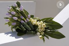 Luxury centerpiece with lilac and white tuplips, aspidistra leaves, xerophyllum tenax.