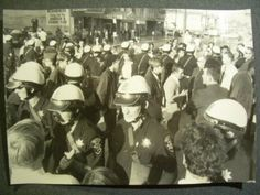 Oakland CA. Inductees enter selective service center under heavy OPD police guard with draft potesters present during Vietnam War. October 1967