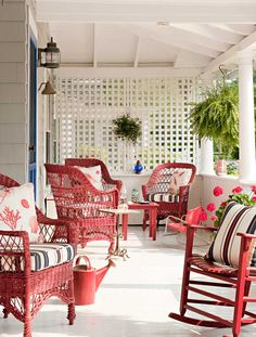 The red,and white porch features Bar Harbor-style wicker furniture~