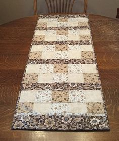 Quilted floral country table runner, measuring 42 x 15. This runner has been created in an assortment of brown, beige and cream floral prints and would make the perfect accent to your dining room, breakfast nook or living room. The colors in this runner feature rich hues of brown