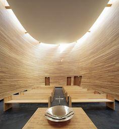 Interior da Capela Kamppi, em Helsinque, Finlândia. A capela tem paredes curvadas, como se suavemente abraçasse o visitante e o protegesse da vida agitada do exterior. Os tons de madeira exalam calor natural, que é amplificado pela luz solar indireta que entra pela parte superior. Arquitetura: K2S Architects.  Fotografia: Tuomas Uusheimo.