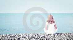 Sad lonely  young beautiful woman sitting back on beach the sea
