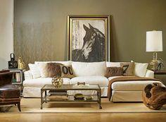 parede de concreto que nem a da bela para sala sofá longe de couro escuro poltrona de couro claro mesa de centro dourada almofadas tons de bege abajur quadro grande p&b&marrom