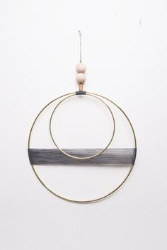"Beautiful brass and waxed cord wall hanging with raw wood and vintage brass bead detail. Measurements: - Larger brass circle is 10"" - Smaller brass circle is 6"" - Beaded hanger above circles is 6"" - T"