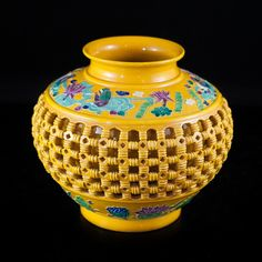 Lot #205: Qianlong Marked Porcelain Vase DESCRIPTION: Double Walled Lattice Porcelain Vase with Qianlong period mark featuring imperial yellow glaze motif. Around the neck and base are multicolored floral banners of animal figures carefully painted in turquoise, pink, green and purple. Marked on the bottom with qianlong mark.  CIRCA: 19th ct ORIGIN: China DIMENSIONS: 10″ Diameter