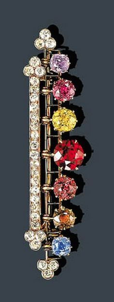 AN ANTIQUE DIAMOND AND GEM-SET BROOCH, JAQUES MARCUS Jaques Marcus The old mine-cut diamond bar, suspending a line of graduated old mine and old European-cut multicolored sapphires, and a demantoid and hessonite garnet mounted in gold, circa 1885 Signed Jaques Marcus