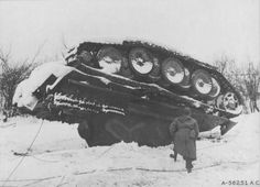 """Captain James B. Lloyd, liaison officer with the 370th Fighter Group, examines and overturned German """"Panther"""" tank that fell victim to an attack by USAAF P-38 Lightning fighters during the Battle of the Bulge, Dec 1944. Mastery of the air gave Allied forces the decisive edge against the failing German defenders."""