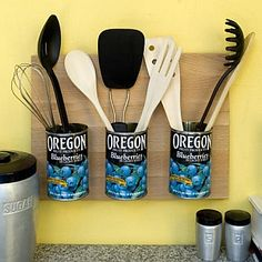 transform clean, empty tins into a piece of folk art that doubles as a cooking utensil holder -  cover with vintage labels and bolt to a wooden cutting board with a frame hanger on the back - display on the wall near the stove