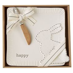 2-piece set. Ceramic cheese plate features layered ceramic bunny icon with hand-painted stitching detail, resist 'happy' sentiment and fluted edges. Arrives gift boxed with mango wood spreader with vintage silver-plate handle.