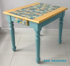 Andrea Guerriero - DRE DESIGNS  www.dredesigns.ca  www.facebook.com/dredesigns.ca  Small end table painted using Annie Sloan Arles & Provence.  Scrapbook paper was decoupaged on top and then varnished.  Gorgeous glass knob from Porta Verde Studio used for the drawer