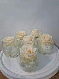 Tafel versiering  van klein glaasjes gevuld met witte hortensia parels en enkele open vendela roos gemaakt door  www.bloemenweelde-amsterdam.nl