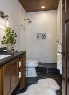 Utilitarian American Classically designed bathroom with custom open shelve vanity with tongue and groove ceiling stained in the same finish. Matte finish subway tiles black penny tile shower floor by #WestBayHomes chic understated industrial luxury