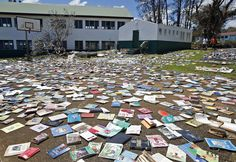 Paul Alexander Hatyay (C), the headmaster, and teacher of Central School, lays out books to dry in the sun after the roof of the school's library was blown away by Cyclone Pam in Port Vila, the capital city of the Pacific island nation of Vanuatu.