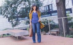 look de street style con chaqueta con aberturas en la espalda y tejido de vuelo en color mostaza, top en azul lavanda oscuro con volantes en los laterales, pantalones denim acampanados, bolso estilo shopping de cuero