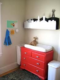 storage solutions for small nursery - I think this dresser style changing table would work well since it can be locked d store toys & extra diapers & wipes & I like the shelf with the Lynn city scape idea!