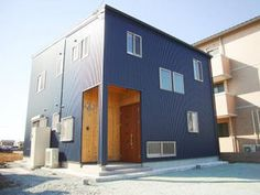 ネイビーブルーの外壁が珍しい家 正面はあえて軒を出さず シンプルな