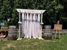 Antique white arbor with fabric hanging down and whiskey barrels on each side